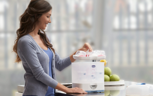 Woman standing in a kitchen with an electric steriliser